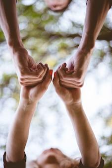 Uma cena vertical de um casal de mãos dadas com um fundo desfocado