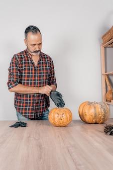 Uma cena vertical de um homem adulto usando luvas de látex e se preparando para esculpir uma abóbora para o halloween