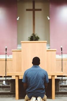 Uma cena vertical de um homem afro-americano orando na igreja