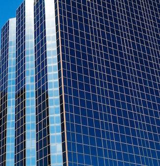 Uma cena vertical de uma torre alta com janelas azuis