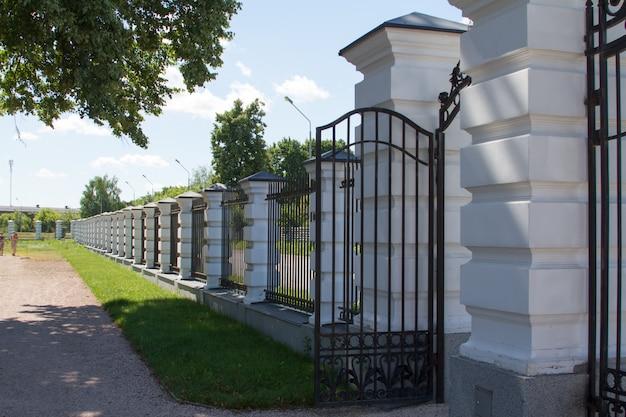 Uma cerca com colunas e uma treliça perto da estrada de asfalto e parque inglês