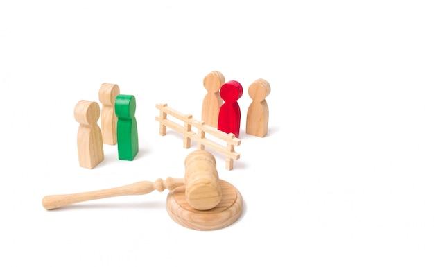 Uma cerca de madeira divide os dois grupos que discutem o caso.