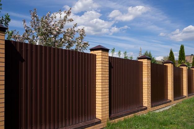 Uma cerca de metal marrom com postes de tijolos contra um céu azul