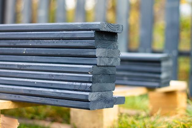 Uma cerca pintada de cinza escuro tábuas empilhadas do lado de fora