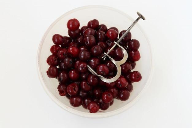 Uma cereja fresca e sem sementes está localizada em uma tigela, remoção de ossos de cerejas por adaptação especial