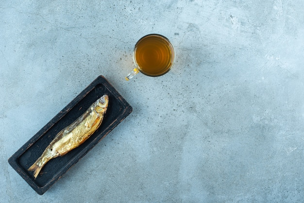 Uma cerveja de copo ao lado do peixe num prato de madeira, na mesa azul.