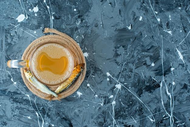 Uma cerveja de copo e um peixe no tripé, na mesa azul.