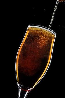 Uma cerveja derramando em um copo em um fundo preto.