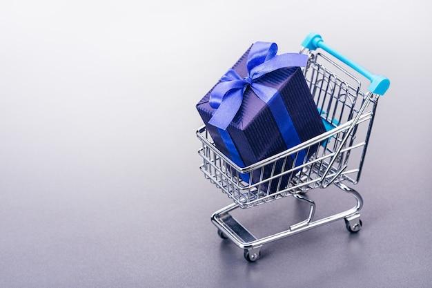 Uma cesta (brinquedo) com presentes em caixa embalada em papel azul.