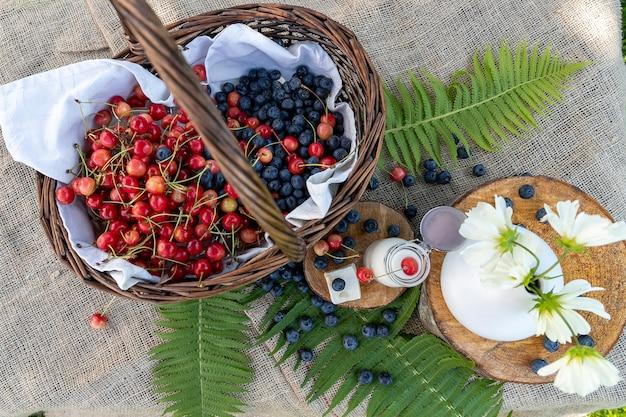 Uma cesta cheia de verão bagas mirtilos e cerejas. abundância de verão.