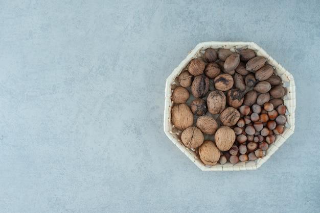 Uma cesta com nozes saudáveis no fundo de mármore. foto de alta qualidade