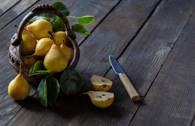 Uma cesta de barro com peras, uma faca e uma pêra em um corte. espaço livre para o texto