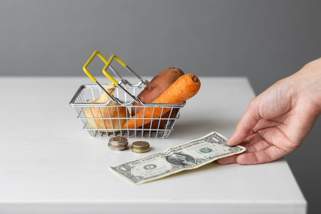 Uma cesta de comida de supermercado de metal com vegetais, papel-moeda e moedas em uma mesa branca
