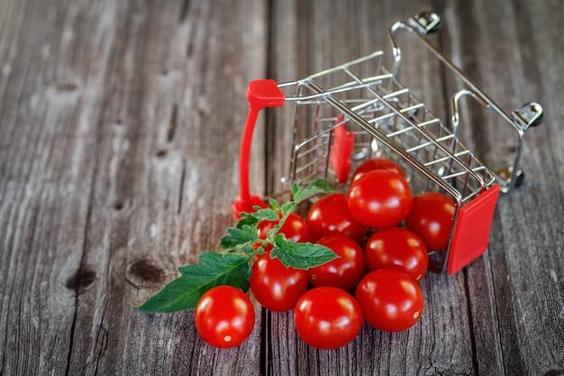Uma cesta de compras caída com tomate cereja em um fundo de madeira. mercado.