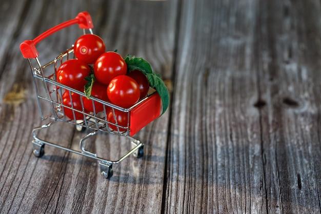 Uma cesta de compras cheia de tomates cereja em um fundo de madeira