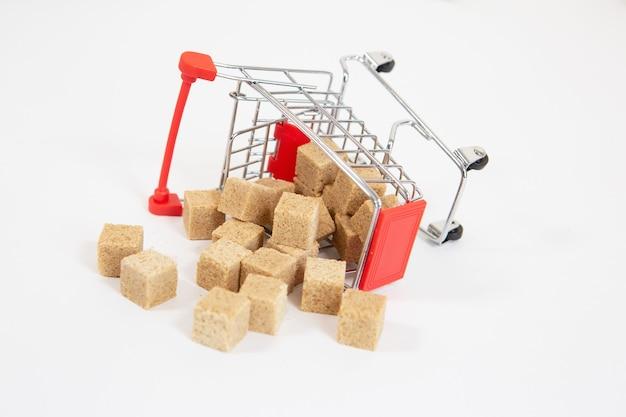 Uma cesta de compras de supermercado tombada com cubos de cana-de-açúcar espalhados