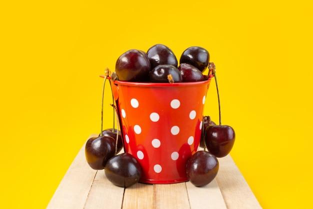 Uma cesta de frente com cerejas azedas e maduras em amarelo, cor de frutas de verão