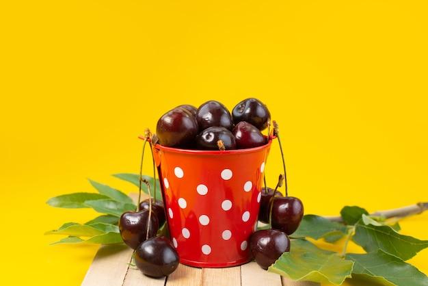 Uma cesta de frente com cerejas azedas e suaves em amarelo, cor de frutas azedo de verão