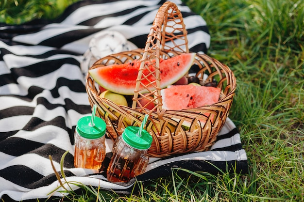 Uma cesta de frutas e copos com bebida no piquenique ao ar livre