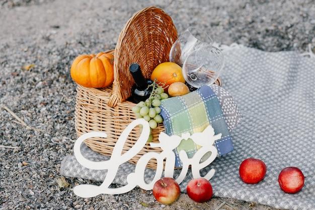 Uma cesta de frutas e vinho para um piquenique na praia