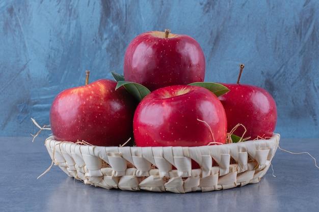 Uma cesta de maçãs e folhas na superfície escura