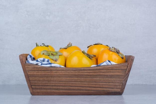 Uma cesta de madeira cheia de caquis doces em fundo branco. foto de alta qualidade