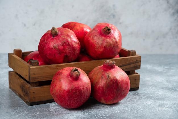 Uma cesta de madeira cheia de frutas doces de romã madura.