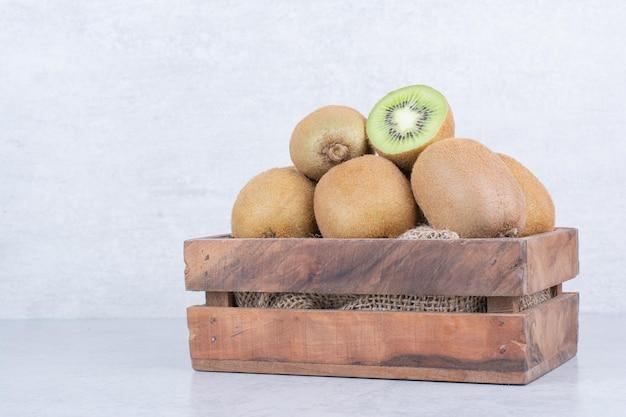 Uma cesta de madeira cheia de kiwi fresco em branco