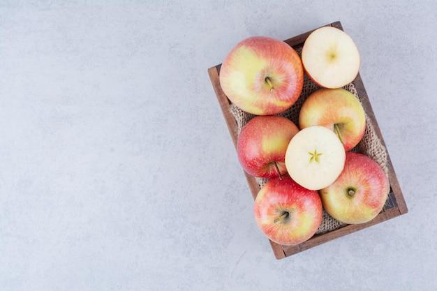 Uma cesta de madeira cheia de maçãs em fundo branco. foto de alta qualidade