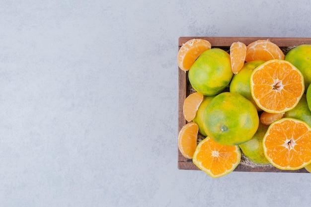 Uma cesta de madeira cheia de tangerinas fatiadas em fundo branco. foto de alta qualidade
