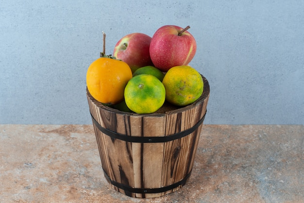 Uma cesta de madeira com frutas doces frescas na mesa cinza.