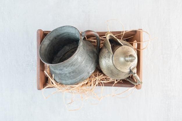 Uma cesta de madeira com uma xícara e um bule antigos. foto de alta qualidade