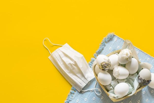 Uma cesta de ovos de páscoa perto da máscara para proteger contra o espaço da cópia do coronavírus. conceito de férias da páscoa durante uma pandemia.