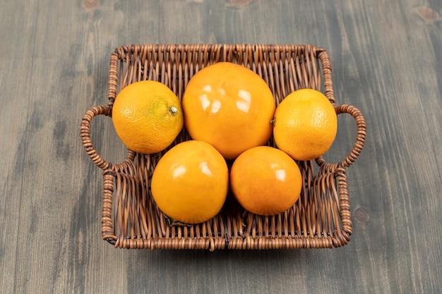 Uma cesta de vime cheia de tangerinas frescas em uma mesa de madeira. foto de alta qualidade