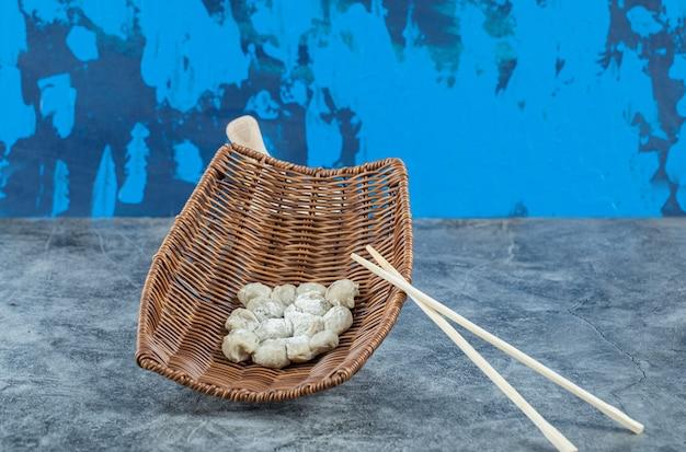 Uma cesta de vime com bolinhos e pauzinhos crus.