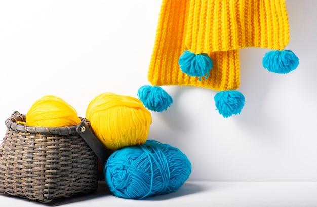 Uma cesta de vime com fios multicoloridos, ao fundo - um lenço de malha amarelo.