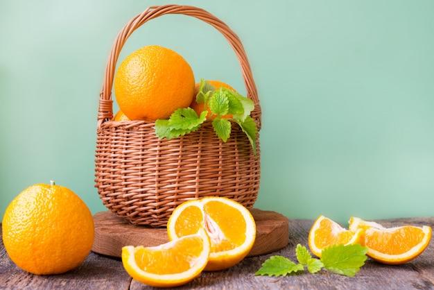 Uma cesta de vime com laranjas e tangerinas dentro fica em uma parede de madeira. foto horizontal.