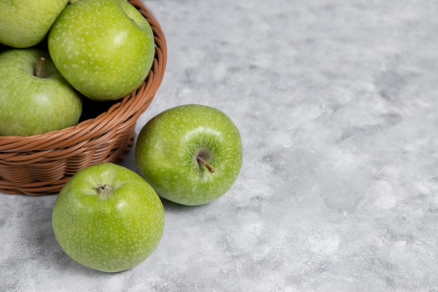 Uma cesta de vime com maçãs verdes frescas na pedra