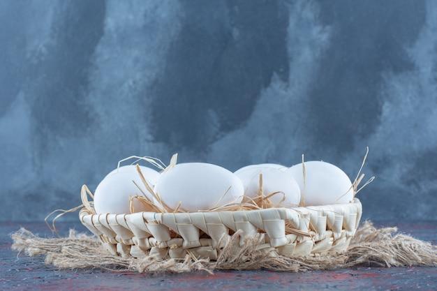 Uma cesta de vime com ovos de galinha crus