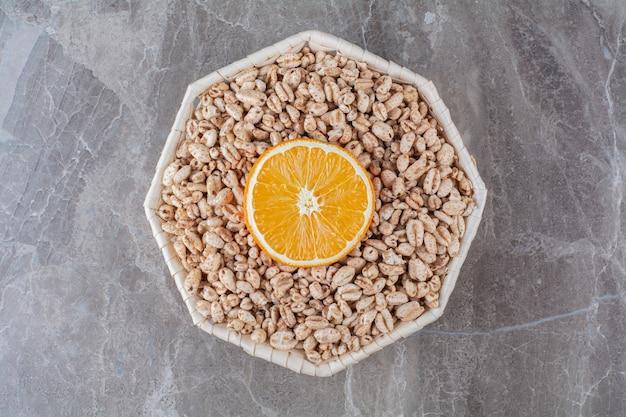 Uma cesta de vime de cereais matinais saudáveis de arroz torrado com uma fatia de fruta laranja.