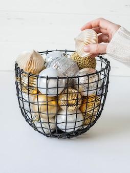 Uma cesta de vime de metal com várias bolas de natal e uma mão feminina