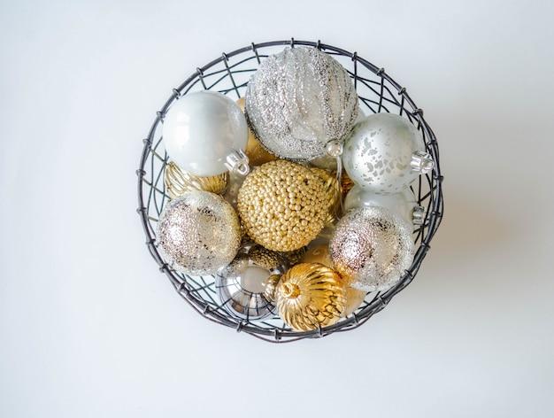 Uma cesta de vime de metal com várias bolas de natal em ouro e prata. foco seletivo