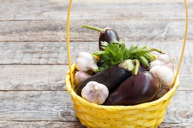 Uma cesta de vime de verduras do alho da beringela dos vegetais no fundo concreto de madeira na rua.