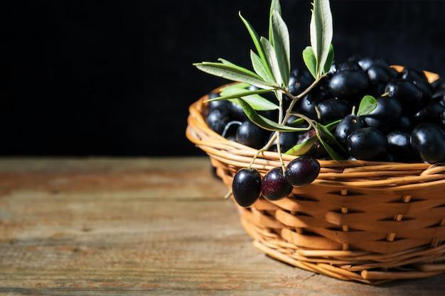 Uma cesta de wiker cheia com azeitonas pretas frescas maduras de puglia, itália, chave baixa