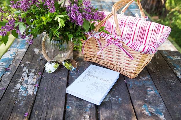 Uma cesta, livro, óculos escuros e um lindo buquê de lilases estão sobre uma mesa velha. fechar-se