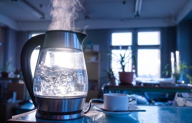 Uma chaleira transparente de água ferve contra o pôr do sol brilhando através da janela