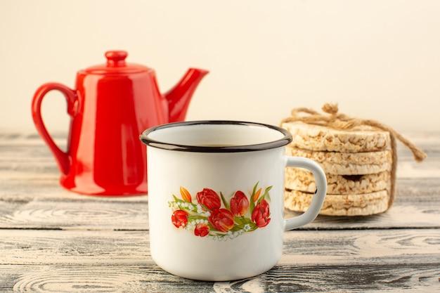 Uma chaleira vermelha de vista frontal com uma xícara de café e biscoitos na mesa rústica cinza bebe cor de café