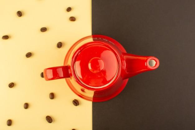 Uma chaleira vermelha de vista superior com sementes de café marrom na mesa amarelo-escuro