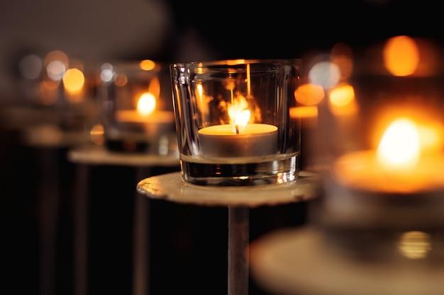 Uma chama de vela acesa em um vidro transparente em uma vela metálica