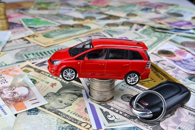 Uma chave de carro e um carro de brinquedo vermelho em uma torre feita de moedas. de várias moedas nacionais e uma nota de dólar simbólica de ouro. do custo de compra, aluguel e manutenção de um carro.